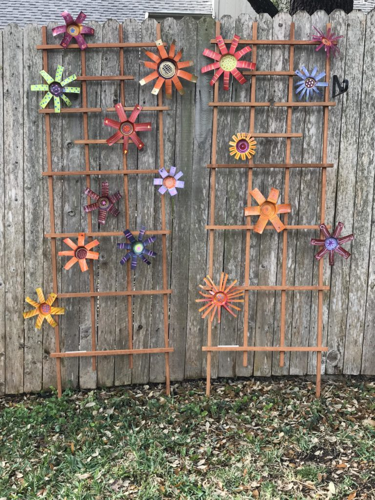 DIY Tin Can Flowers on trellis' against the fence