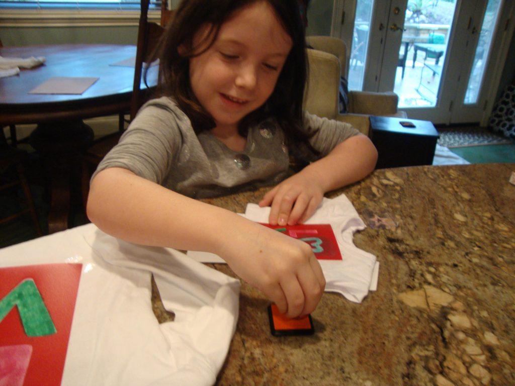Stenciling her dolls tee shirt