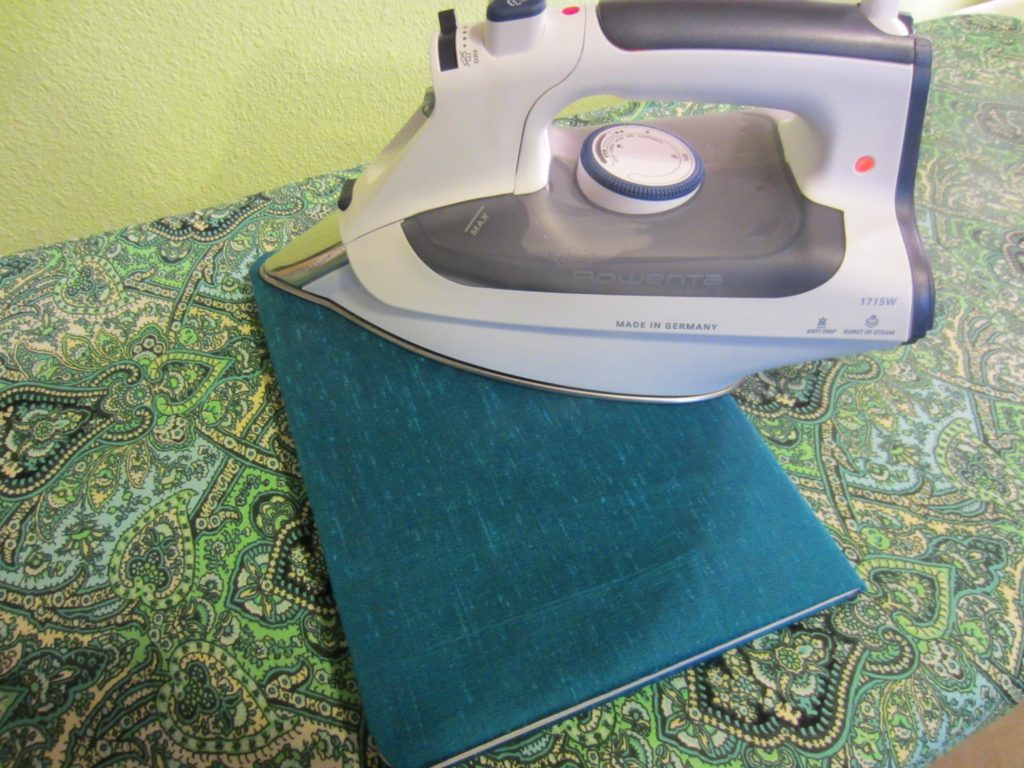 Pressing well to bond the fabric to the book