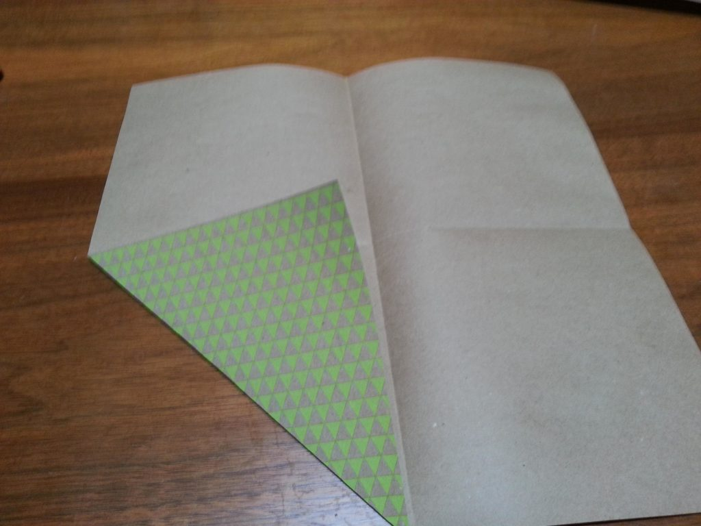 Fold the paper in half the other direction to form 4 squares. Turn in each corner to make triangles