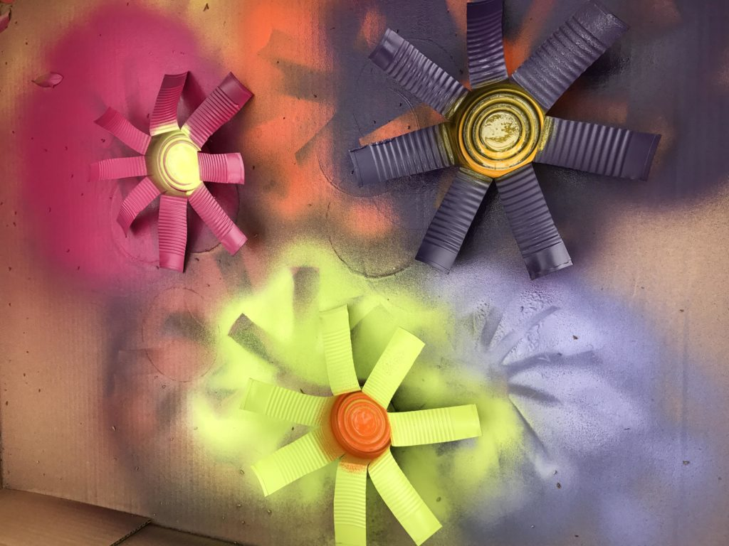 Second layer of paint, painting the centers of the flowers which are the can bottoms