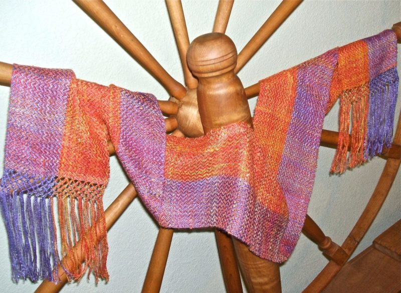 Finished scarf draped over a spinning wheel