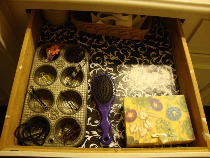 Hair accessories organized in an old muffin tin.