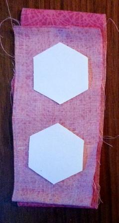 Basting the paper hexagons to the back of your fabric strips