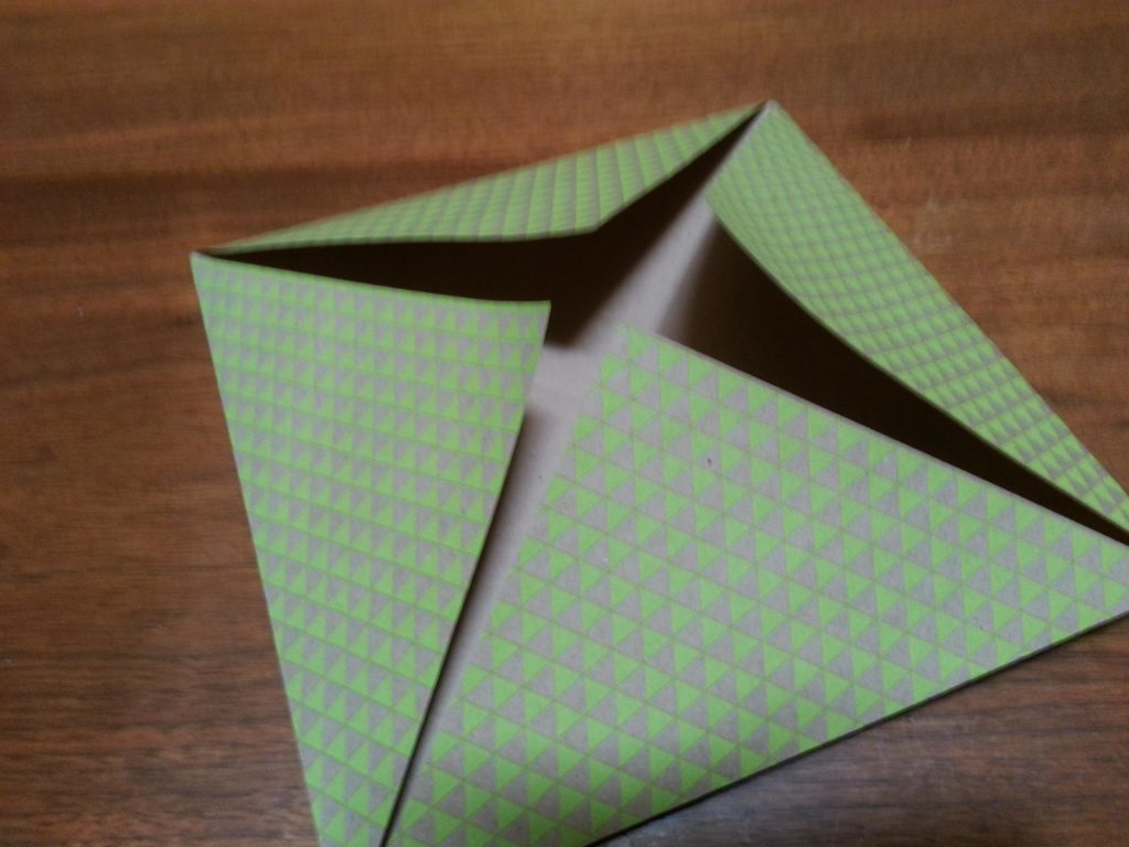 Fold in all four corners to center to form a square
