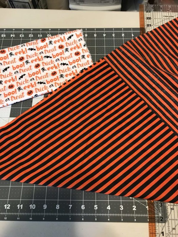 Laying the fabric out for the reversible Halloween scarf