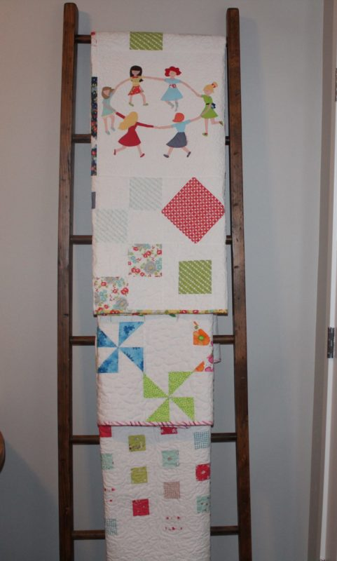 Quilts hung on a ladder