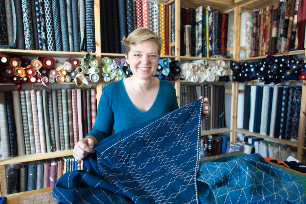 Carol Ziogas in her shop with a piece of her Sashiko