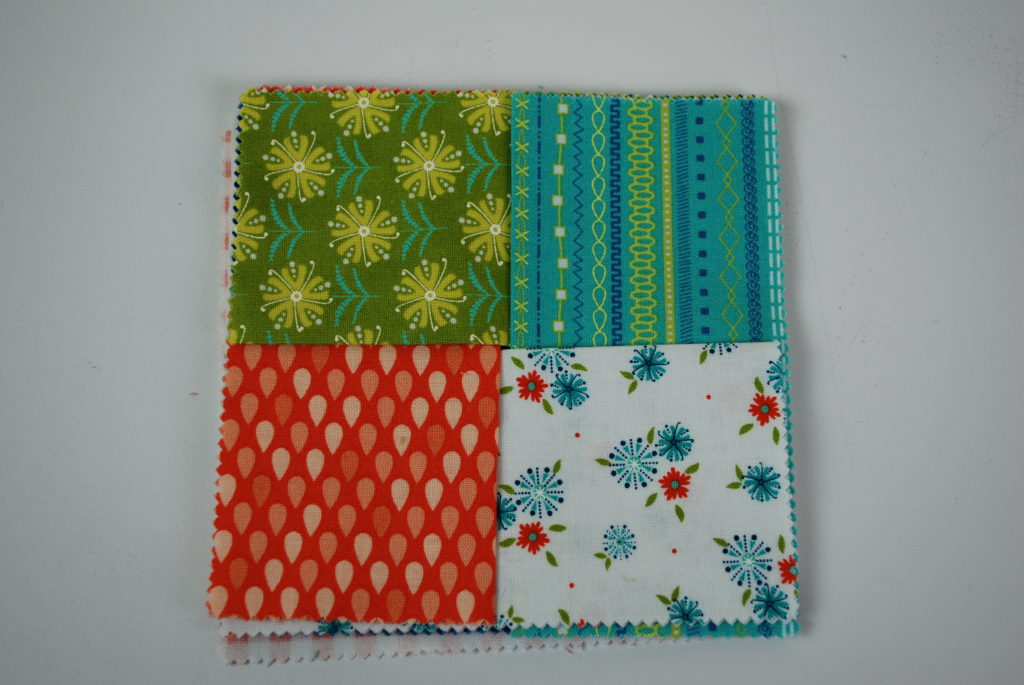 Laying out the top 4 fabrics to make the flaps to be a wine coaster