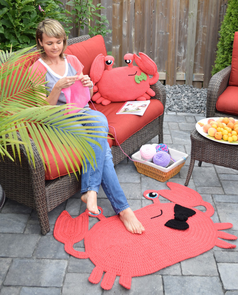 Ira crocheting on her patio with crocheted lobster rug and pillow