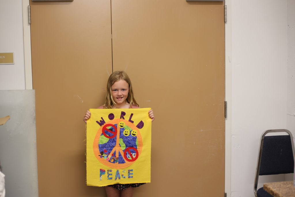 A young girl and her finished quilt block