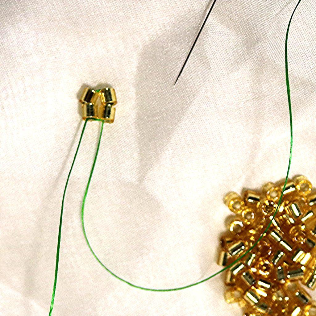 The first loop of 4 beads in making a herringbone rope