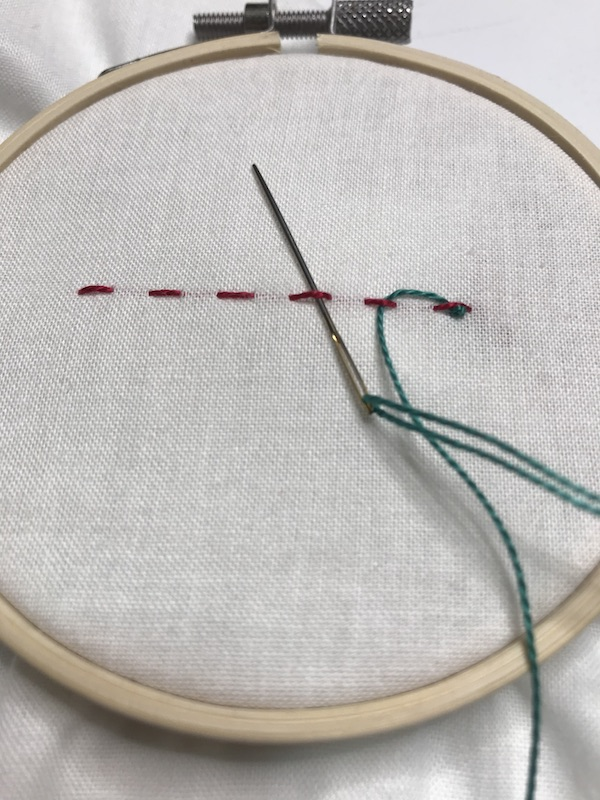 Then lace the second thread up through the next stitch