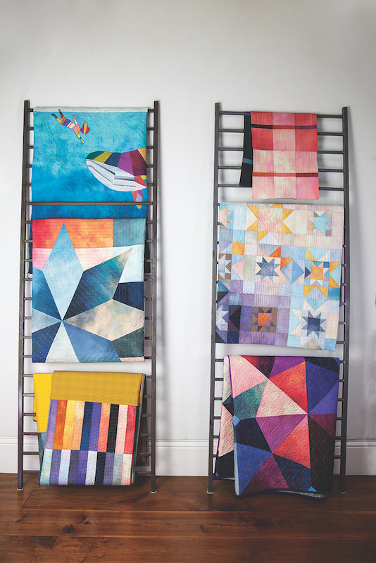 Quilts being displayed on ladders