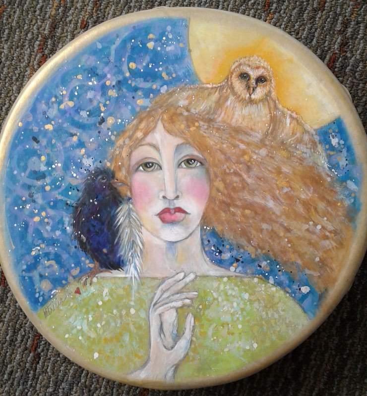 Woman and owl painting on a drum