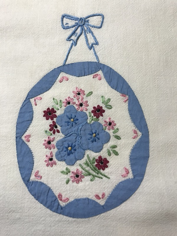 Vintage tea towel with both applique and embroidered flowers