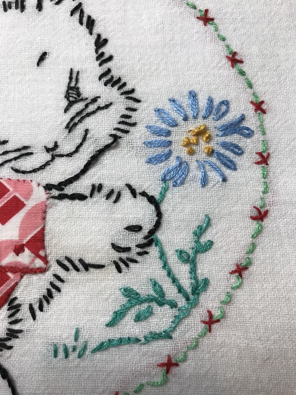 Close up of daisy stitch flower on a vintage tea towel with a bunny