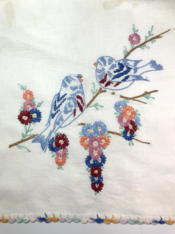 Birds and flowers embroidered on a vintage kitchen towel