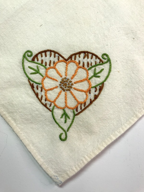Flower embroidered on the corner of a vintage tablecloth in a stem stitch