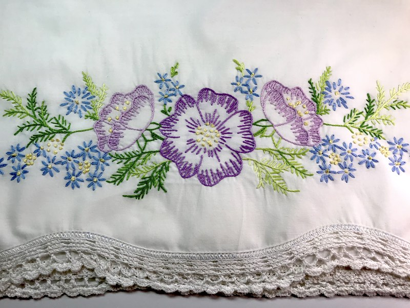 Embroidered flowers on the edge of a pillowcase