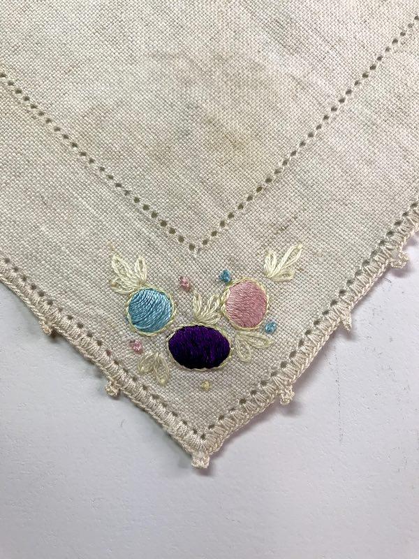 Satin stitched flowers on the corner of a vintage dresser cloth