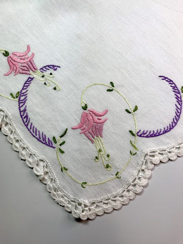 Satin stitched fuchsia on the corner of a vintage dresser cloth