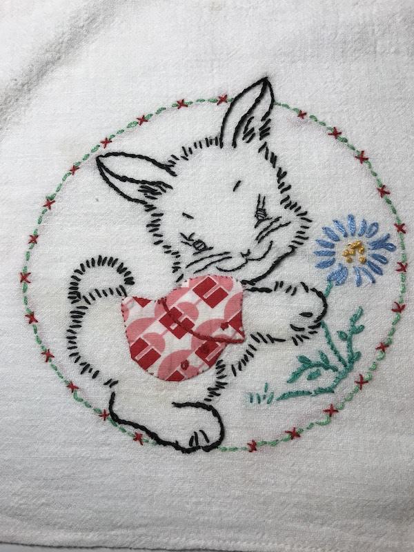 Daisy stitch flower on a vintage tea towel with a bunny