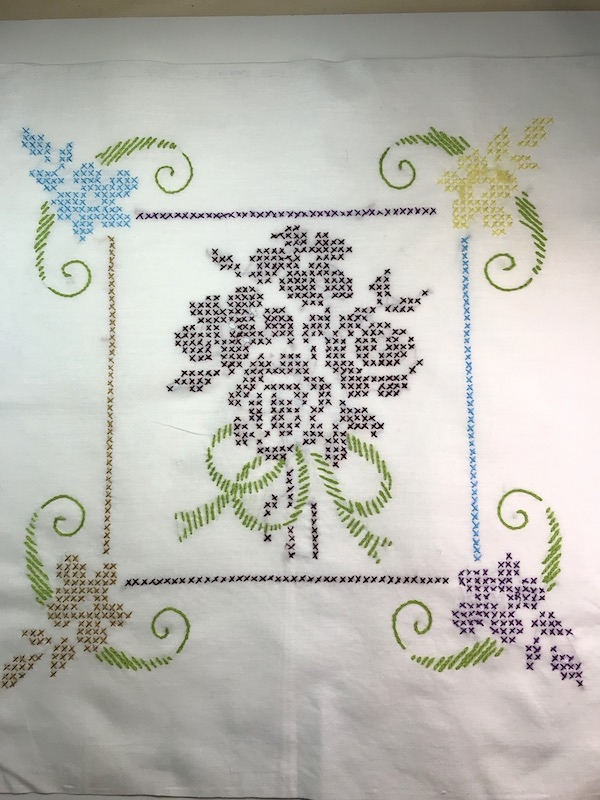 Cross stitches flowers in the center of a vintage card table tablecloth