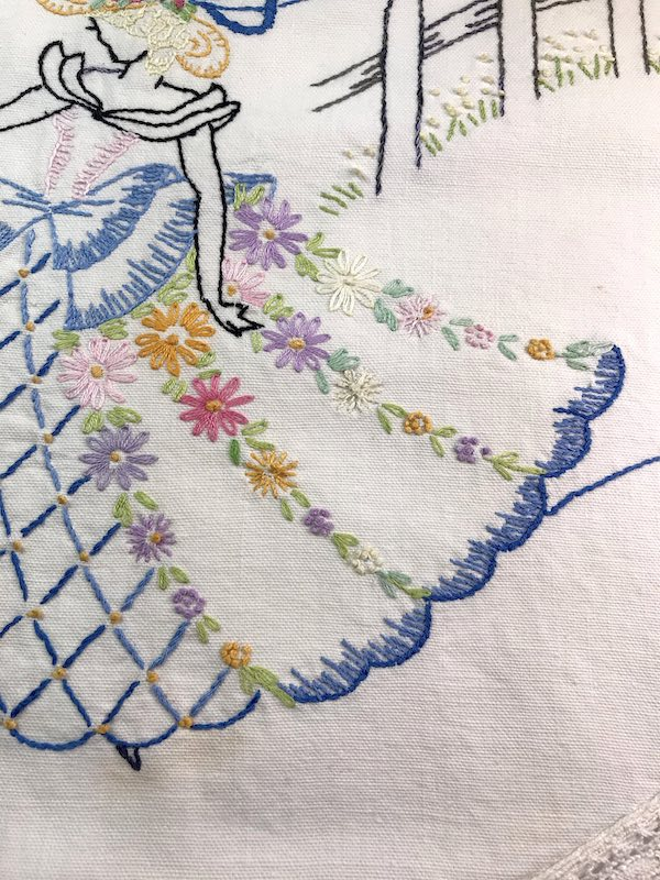 Close up of daisy stitch flowers on the skirt of a lady on a vintage dresser scarf