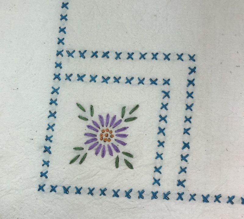 Embroidered flower with cross stitch border on a vintage tablecloth
