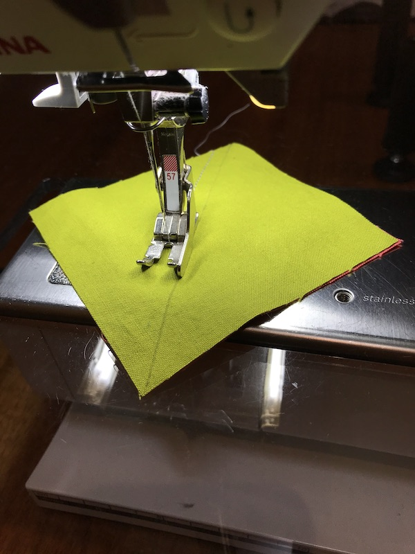 Sewing the first seam for making two half square triangles at once