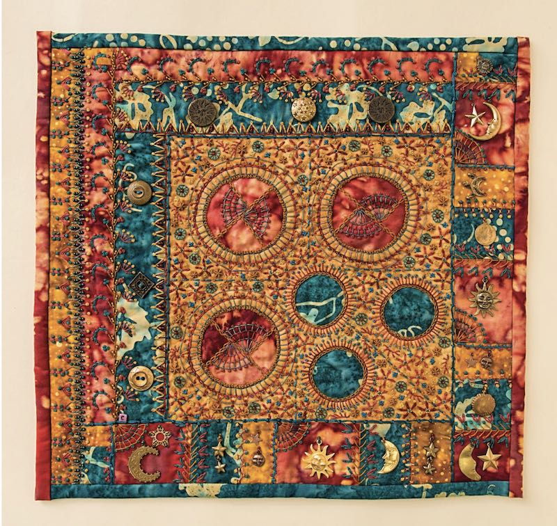 Orange and turquoise quilt block with embroidery