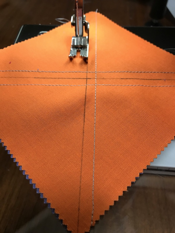 Sewing the fourth seam for half square triangles eight at a time with a charm pack