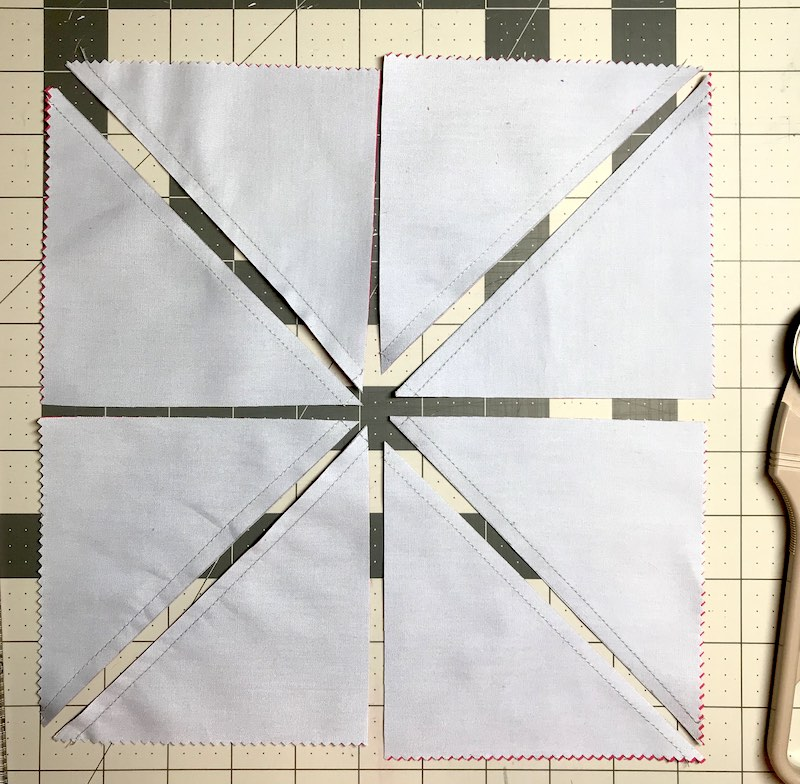 Half square triangles eight a time from a layer cake all cut and ready to be pressed and trimmed