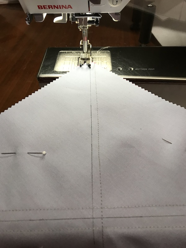Sewing the fourth seam to make eight half square triangles at a time from a layer cake