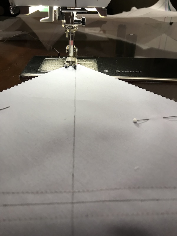 Sewing the thrid seam to make eight half square triangles at a time from a layer cake