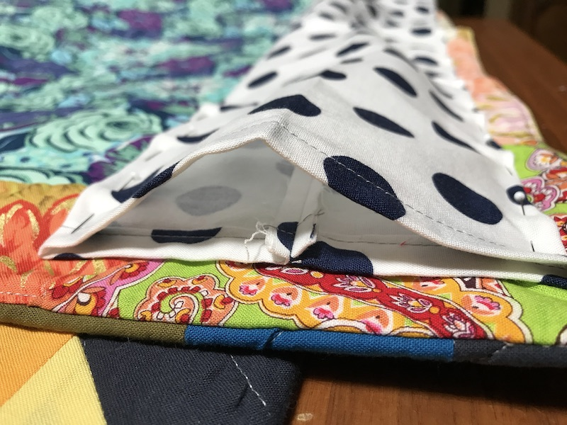 Pinned quilt sleeve to quilt back