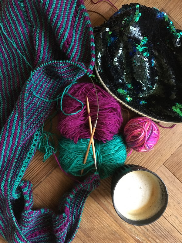 Knitting a teal and purple shawl with a cup of coffee